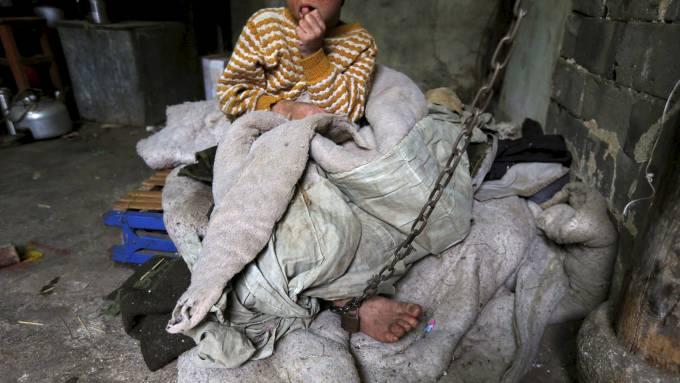 """Il posto dove He Zili passa la sua giornata: non la si può chiamare """"cameretta"""" o """"stanza"""", c'è solo una coperta consumata e l'allaccio alla catena che non lo abbandona mai"""