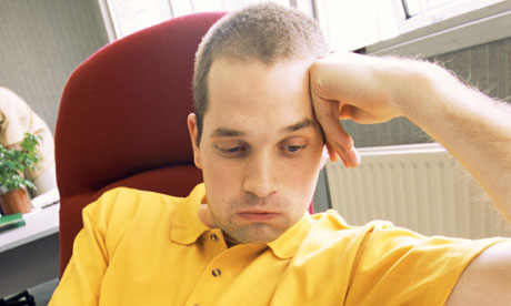 Man sitting at desk looking bored