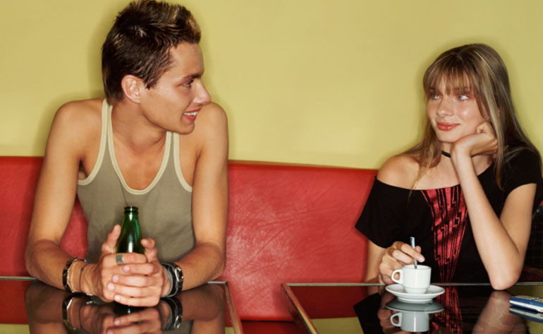 Teenage Man and Woman Sitting Side by Side in a Cafe and Flirting